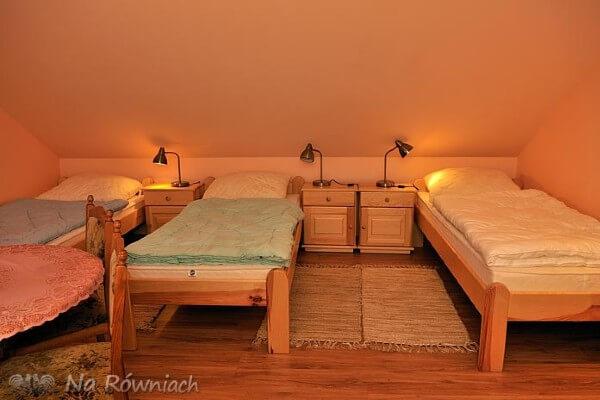 Pokój z trzema łóżkami i lapmpki