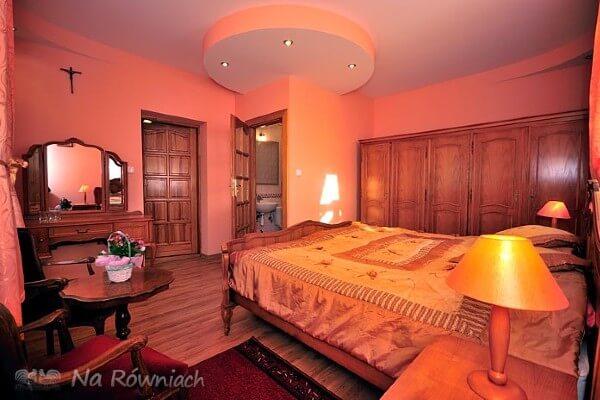 Pokój z podwójnym łóżkiem wykończony drewnem